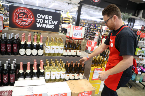 BevMo! employee restocking red and white wines