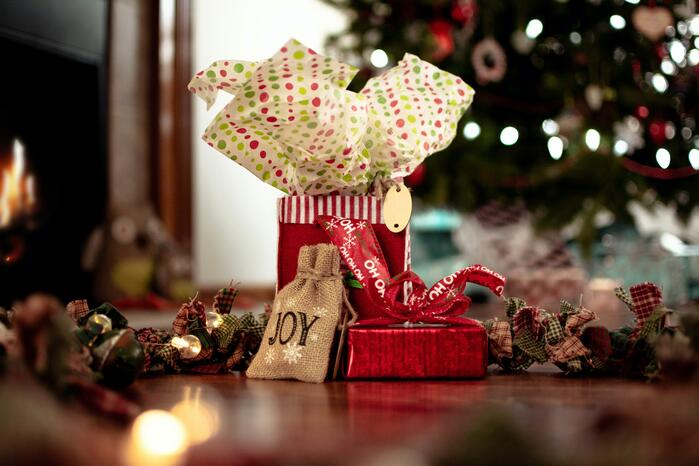 """Red gift bags, one with """"JOY"""" on the front, in front of a Christmas tree."""